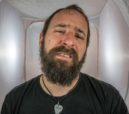 A bearded and broken man with eyes wide open