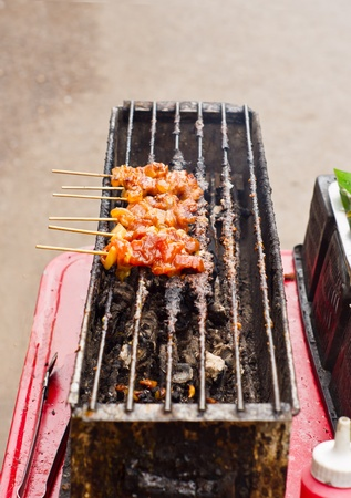 moo ping, a thai food make by  pork grilled on charcoal photo