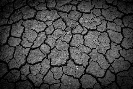 splitting up: dark Cracked soil of desert  Stock Photo