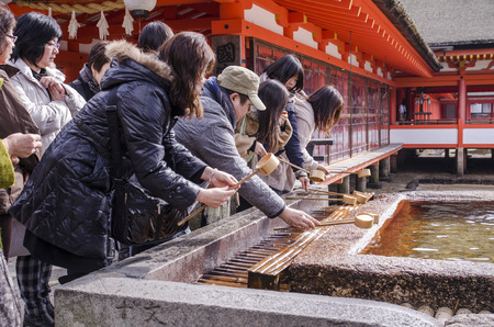 ITSUKUSHIMA SHRINE, MIYAJIMA - DECEMBER 24 : Japanese people washing hand in a temple on December 24, 2013 in Itsukushima Shrine, Miyajima, Hiroshima .