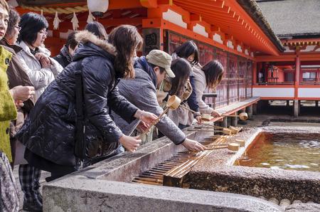 ITSUKUSHIMA SHRINE, MIYAJIMA - DECEMBER 24 : Japanese people washing hand in a temple on December 24, 2013 in Itsukushima Shrine, Miyajima, Hiroshima .