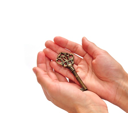 Beautiful bronze key in hands isolated on white background photo