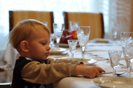 helps: Kid covers table to the birthday, helps arrange cutlery Stock Photo