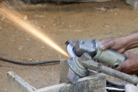 grinder machine: A man shapen the  lawnmower by grinder machine  Stock Photo