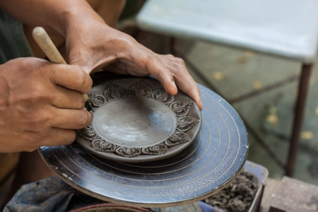 Potter is molding the clay and craving the pattern on it