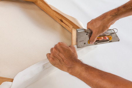Artist stretch canvas and fix it with staple Stock Photo