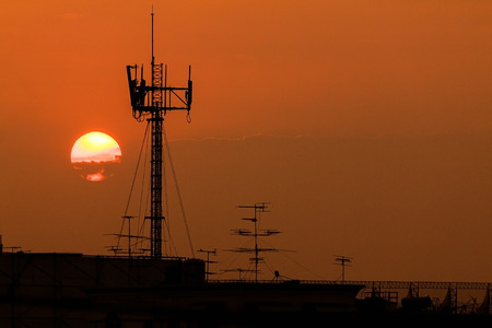 Wireless broaband antenna on the roof with sunset background