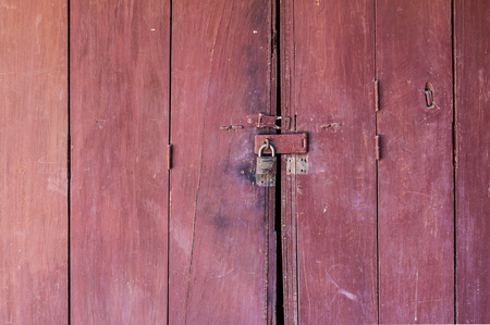 colsed old red wooden door in Thailand photo