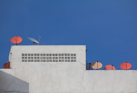 Many satelite dish on the roof top of building in Thailand photo