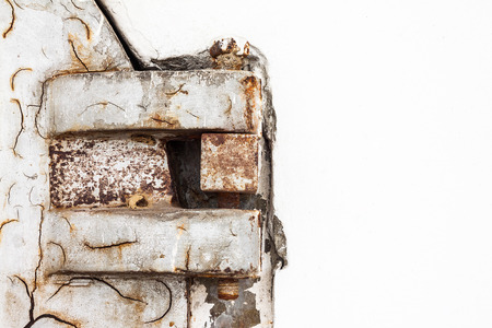Rusty and old metal hinge of crematory door with white cement wall photo