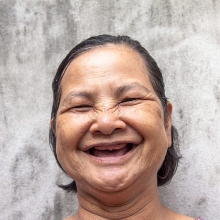 Close up portrait of 60 years old Thai woman laughing