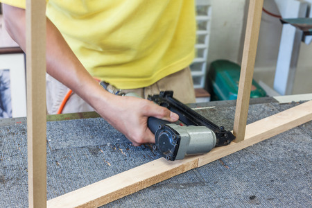 strengthen: Worker using air nailer shooting nail into log for strengthen holding of wooden frame