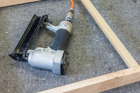 carpentery: Old air nailer with wooden frame on table