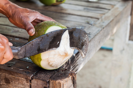 Man,show only hand, chopping coconut by big knife
