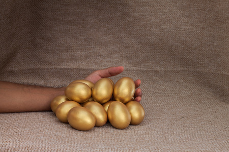 hand lay: Human hand lay down closed to heap of golden egg on brown sack background Stock Photo