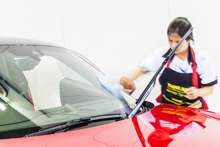 Nonthburi,Thailand - March 26th, 2015: Worker cleaning windshield of  Porsche 911 Carrera 4 GTS ,an exceptional performance carr,showed in Thailand the 36th Bangkok International Motor Show on 26 March 2015 Éditoriale
