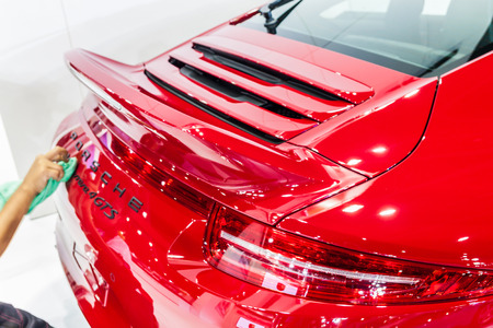 Nonthburi,Thailand - March 26th, 2015: Worker cleaning rear of  Porsche 911 Carrera 4 GTS ,an exceptional performance carr,showed in Thailand the 36th Bangkok International Motor Show on 26 March 2015