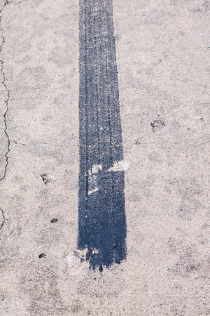 black trace of track tire brake on concrete road photo