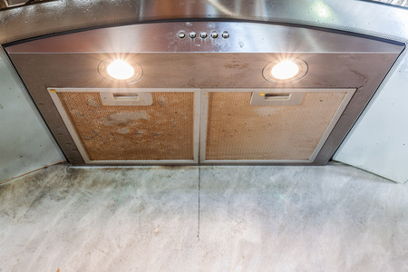 stainless steel range: Cooker hood above stove in kitchen