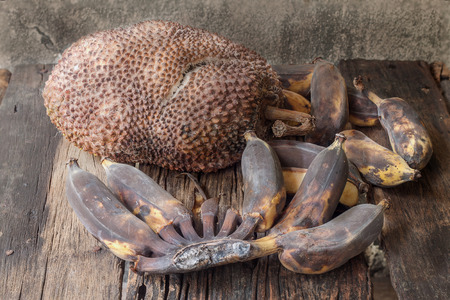 bad banana: Rotten jackfruit and banana on wooden floor and old cement wall Stock Photo