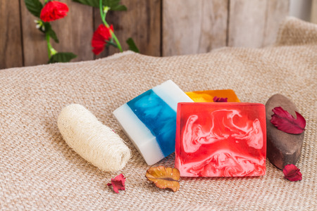 luffa: Homemade soap, luffa and stone body scrub product for spa on towel with wooden background