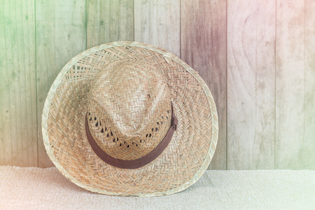 coolie hat: Wicker hat on brown fabric lean against wooden background,vintage tone