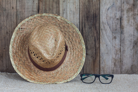 coolie hat: Wicker hat with eye glasses on brown fabric lean against wooden wall background