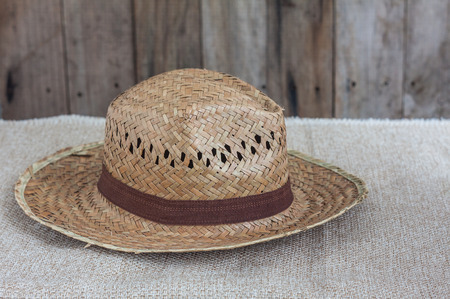 coolie hat: Wicker hat on brown fabric and wooden background
