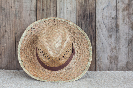 coolie hat: Wicker hat on brown fabric lean against wooden background, Stock Photo