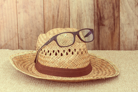 coolie hat: Wicker hat with eye glasses on brown fabric and wooden wall background