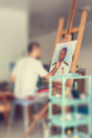 artist: Blur of artist painting a man portrait on easel in studio Stock Photo