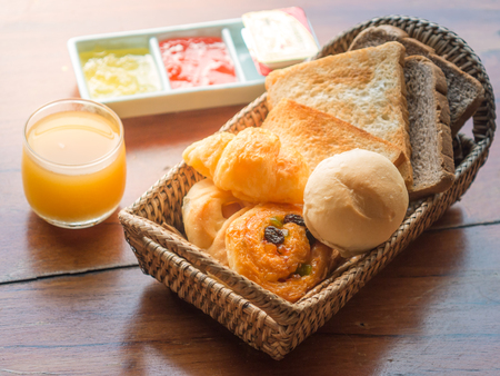 table glass: Set of bread in wicker basket with jam and orange juice on wooden table Stock Photo