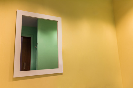 bathroom: Big mirror on empty yellow wall in bathroom Stock Photo