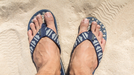 flipflops: Man feet wearing blue flip flops on a beach Stock Photo