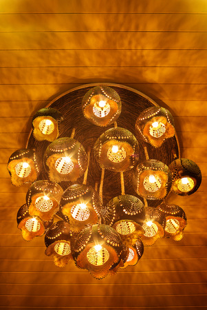ceiling lamp: Ceiling lamp made from carving coconut shell with yellow light and shadow Stock Photo