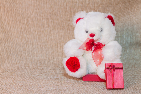 sack cloth: Teddy bear sitting on small red gift box with sack cloth background