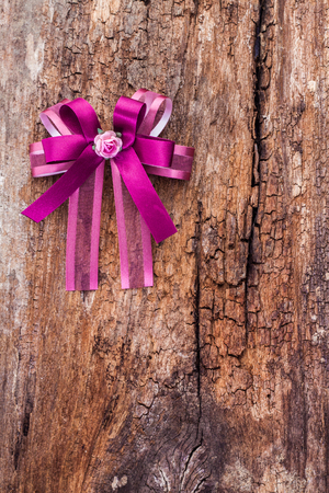 purple ribbon: Purple ribbon on old rough brown wooden board Stock Photo