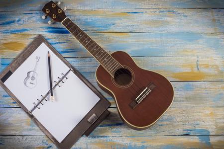 ukelele: Ukulele with notebook with drawing of ukelele on colored wooden background Stock Photo