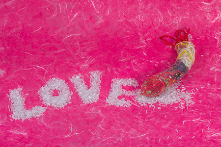 red condom: Love wording arrange by bead with thread bead in condom on pink mulberry paper background