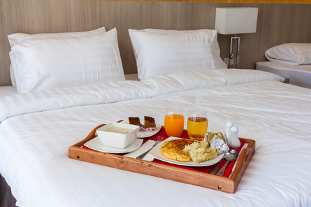 Breakfast set,omlete,bake bean,orange juice,milk and sweat in wooden tray serving on bed