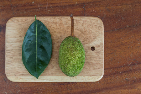 cleave: Immature jackfruit and leaf on wooden chopper block