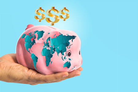 worldmap: Dollar sign over piggy bank with worldmap in male hand on blue with clipping path ( map derived from NASA world map)