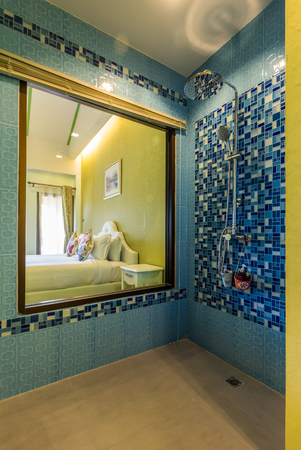 bedroom wall: Modern style of bathroom,shower on blue pattern wall,that can see bedroom through transparent mirror Stock Photo