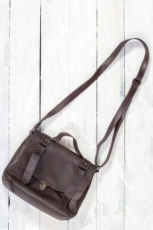 shoulder bag: Brown leather shoulder bag on white wooden background