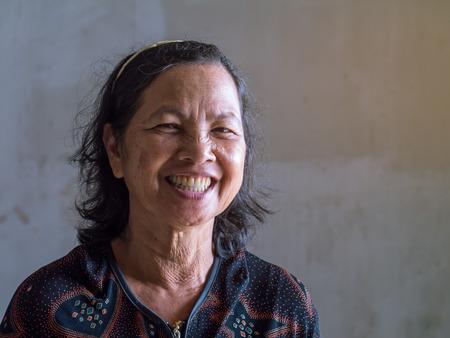 Close up old Thai woman smiling grin with false teeh