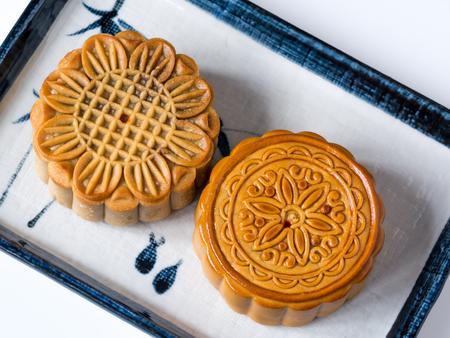 Mid autumn festival dessert, flower pattern moon cakes in white plate on white background