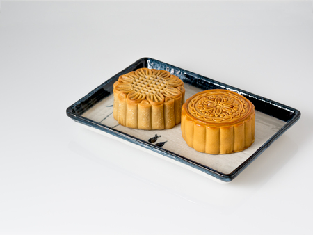 Mid autumn festival dessert, flower pattern moon cakes in white plate on white background with soft shadow Stock Photo