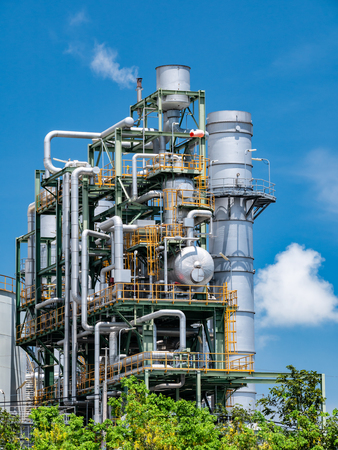 Oil refinery plant behide row of tree and blue sky with cloud, Thailand