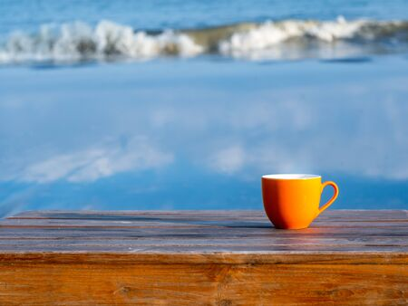 Orange cup of coffee on brown wooden table on beach with surf of blue sea in background. Foto de archivo