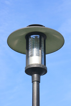 metall and glass: Street lamp with a large screen, blue sky in the background